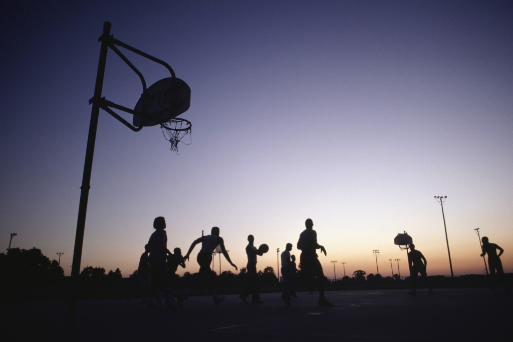 Young people playing basketball at dusk